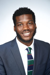 Antwone Roberts smiling in blue pinpoint suit and blue green and red knit tie.